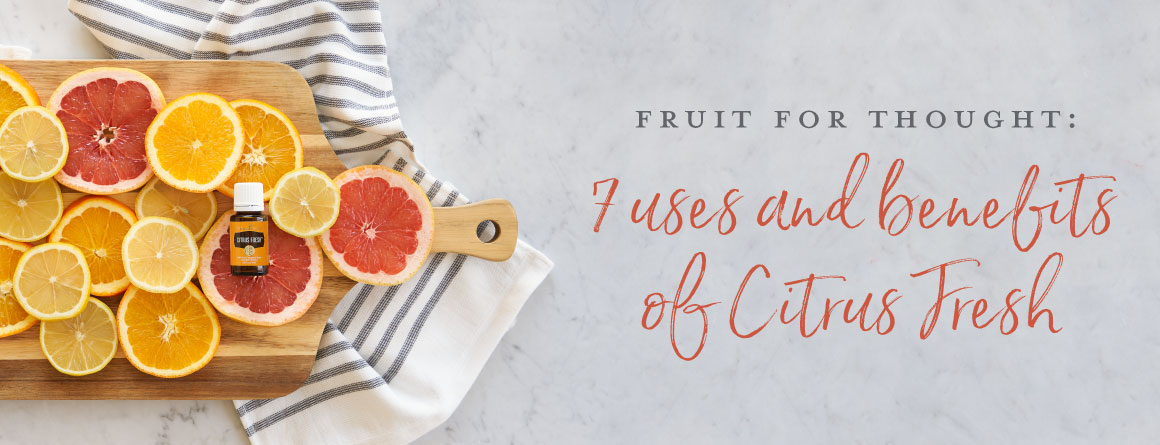 Citrus fruits on a towel and wooden cutting board on a counter top.
