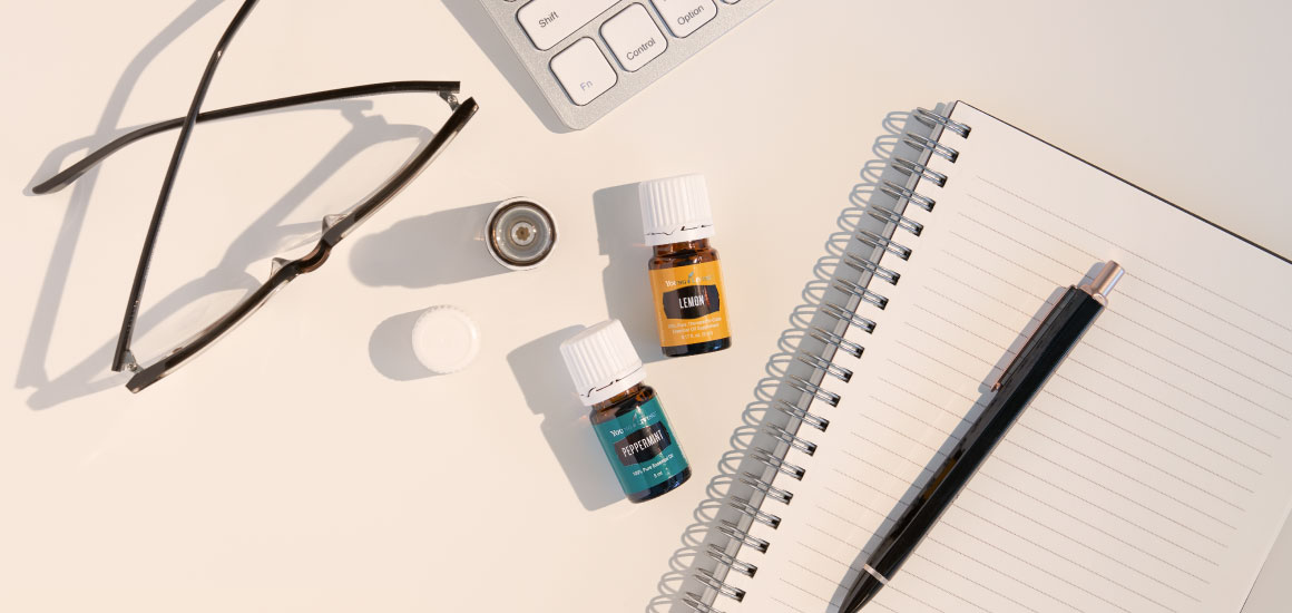 reading glasses, notebook, keyboard and peppermint and lemon essential oil for productivity