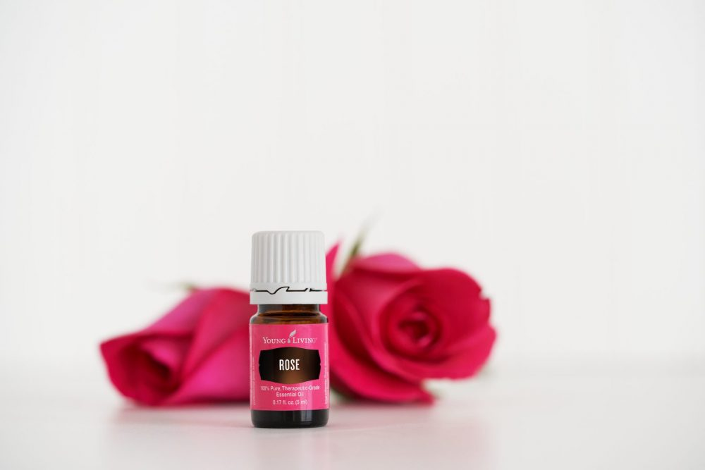a bottle of rose essential oil by roses. learn the benefits of rose oil