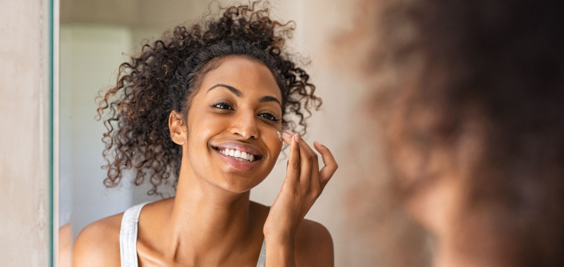 Woman applying Young Living BLOOM moisturizer to her face