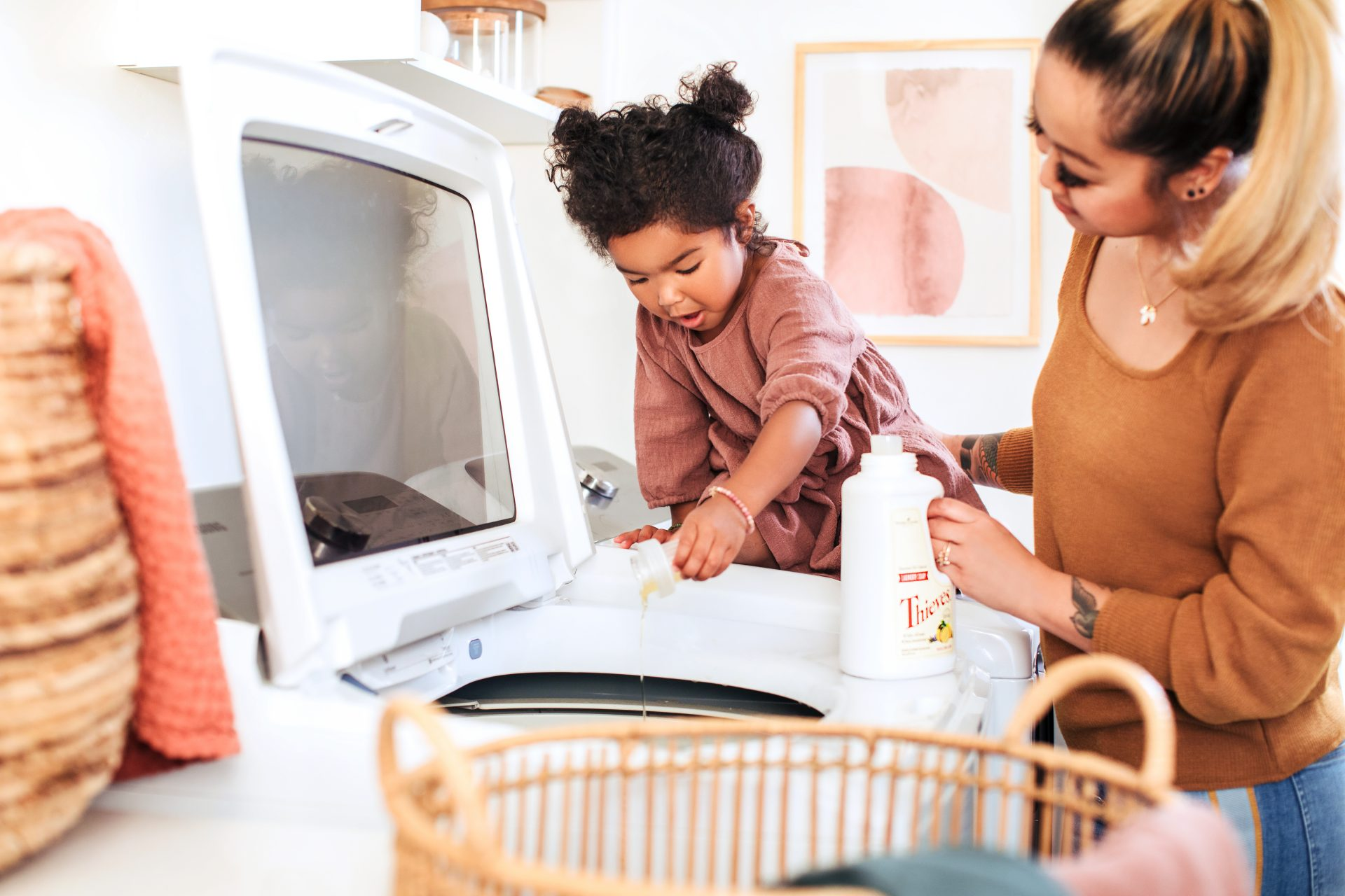 Mom and child doing laundry with Young Living essential oil products